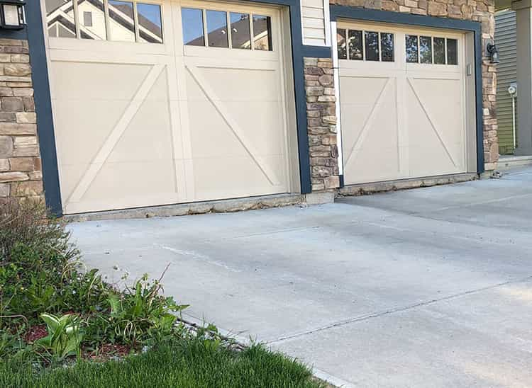 Before situation of a concrete driveway in front of garage doors of a home at Highlands, Lincoln.